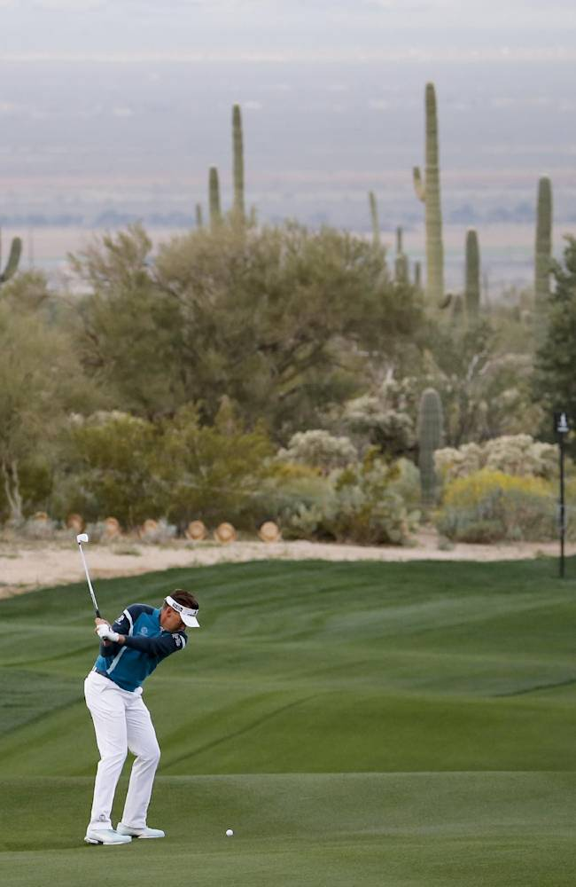 Ian Poulter, of England, hits from the fairway on the second hole against Rickie Fowler during the first round of the Match Play Championship golf tournament on Wednesday, Feb. 19, 2014, in Marana, Ariz