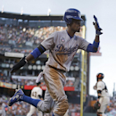 Los Angeles Dodgers' Dee Gordon celebrates after scoring against the San Francisco Giants in the fifth inning of a baseball game Sunday, July 27, 2014, in San Francisco. (AP Photo/Ben Margot)