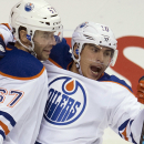 Edmonton Oilers right wing Nail Yakupov (10) celebrates his goal with teammate Benoit Pouliot (67) during the second period of an NHL hockey game against the Vancouver Canucks in Vancouver, British Columbia, Saturday, Oct. 11, 2014 The Associated Press