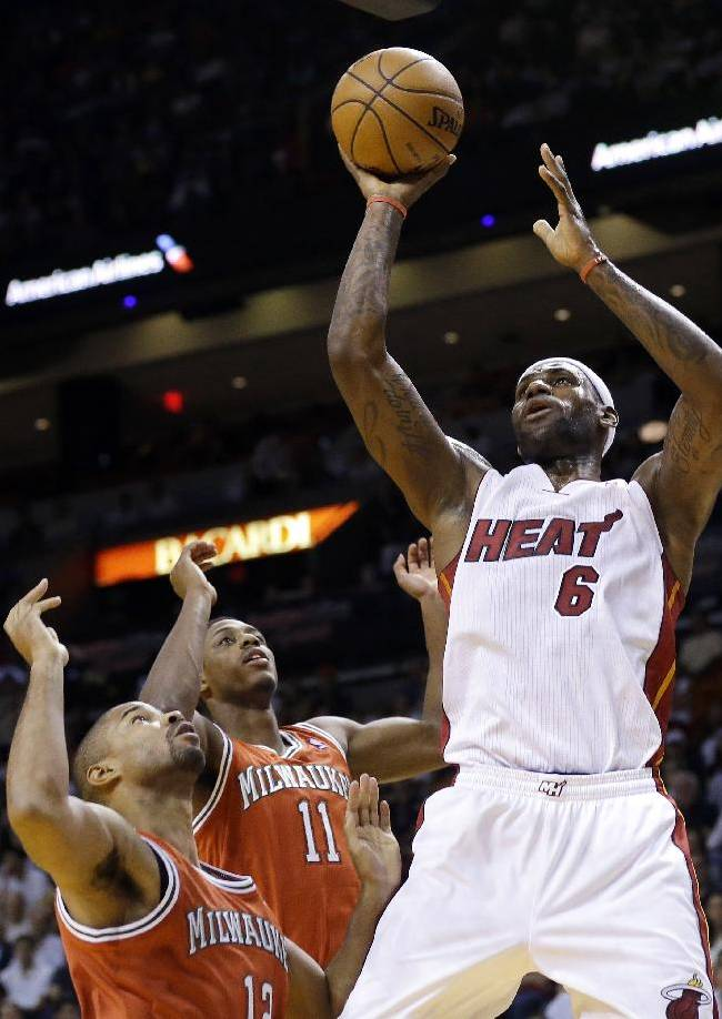 Miami Heat's LeBron James (6) shoots over Milwaukee Bucks' Gary Neal, left, and Brandon Knight (11) during the first half of an NBA basketball game Tuesday, Nov. 12, 2013, in Miami