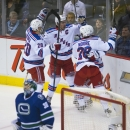 New York Rangers defenseman Ryan McDonagh (27) celebrates his goal as Vancouver Canucks goalie Ryan Miller (30) looks on during the first period of an NHL hockey game, Saturday, Dec. 13, 2014 in Vancouver, British Columbia The Associated Press