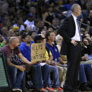 A fan holds a sign behind Dallas Mavericks coach Rick Carlisle, right, who is blocking his view, during the second half of the Mavericks' NBA basketball game against the Golden State Warriors on Tuesday, March 11, 2014, in Oakland, Calif. (AP Photo/Ben Margot)