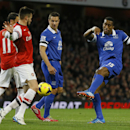 Everton's Sylvain Distin, right, takes a shot on goal during the English Premier League soccer match between Arsenal and Everton at the Emirates Stadium in London, Sunday, Dec. 8, 2013