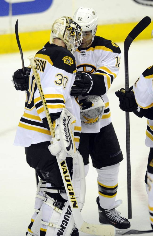 Boston Bruins right wing Jarome Iginla (12) celebrates their 4-2 win over the Washington Capitals with goalie Chad Johnson (30) after an NHL hockey game, Saturday, March 29, 2014, in Washington