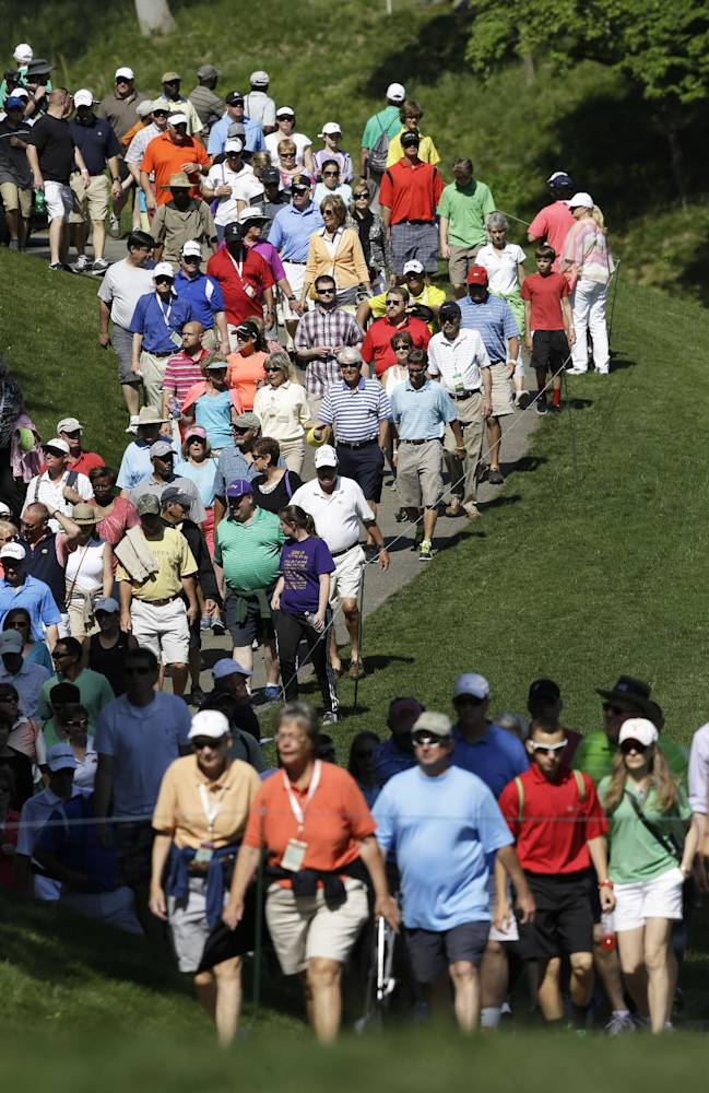 Fans make their way to the eighth green during the third round of the Kingsmill Championship golf tournament at the Kingsmill resort  in Williamsburg, Va., Saturday, May 17, 2014