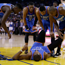 OAKLAND, CA - DECEMBER 18: Kevin Durant #35 of the Oklahoma City Thunder holds his ankle as his teammates check to see if he is okay after he twisted his ankle towards the end of the first half of their game against the Golden State Warriors at ORACLE Arena on December 18, 2014 in Oakland, California. (Photo by Ezra Shaw/Getty Images)