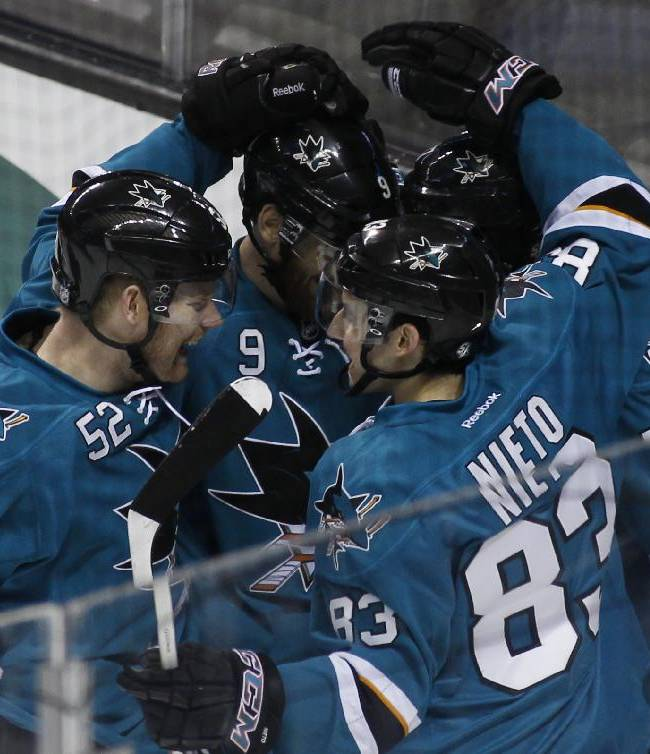 San Jose Sharks' Matt Nieto (83) celebrates with teammates after scoring against the Philadelphia Flyers during the first period of an NHL hockey game, Monday, Feb. 3, 2014, in San Jose, Calif. Sharks' Matt Irwin (52) is at front left
