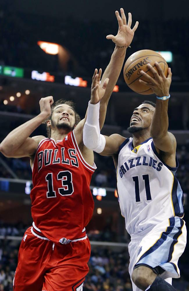 Chicago Bulls' Joakim Noah (13) tries to block a shot by Memphis Grizzlies' Mike Conley (11) in the second half of an NBA basketball game in Memphis, Tenn., Monday, Dec. 30, 2013. The Bulls defeated the Grizzlies 95-91