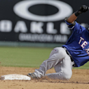 Texas Rangers' Luis Sardinas slides safely into second with a double as Los Angeles Angels' Chris Iannetta has trouble handling the throw during an exhibition spring training baseball game Tuesday, March 4, 2014, in Tempe, Ariz The Associated Press