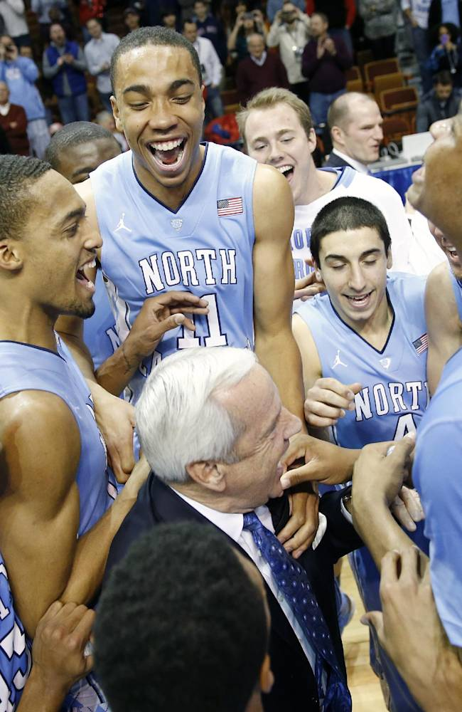 North Carolina head coach Roy Williams, center, celebrates with his team after defeating Louisville 93-84 in the Basketball Hall of Fame Tip-Off tournament championship NCAA college basketball game at Mohegan Sun Arena in Uncasville, Conn., Sunday, Nov. 24, 2013