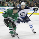 Dallas Stars left wing Antoine Roussel (21) skates with the puck against Winnipeg Jets left wing Adam Lowry (17) during the first period of an NHL hockey game Thursday, Jan. 15, 2015, in Dallas The Associated Press