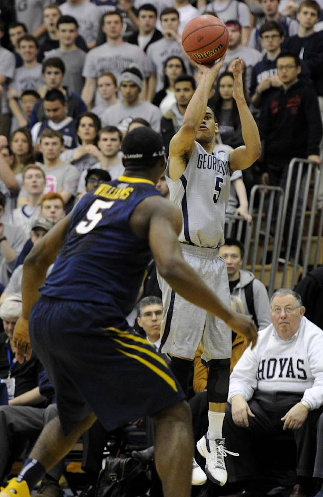 Georgetown guard Markel Starks, right, puts up a shot against West Virginia forward Devin Williams, left, during the second half of an NCAA college NIT tournament first round basketball game, Tuesday, March 18, 2014, in Washington. Georgetown won 77-65