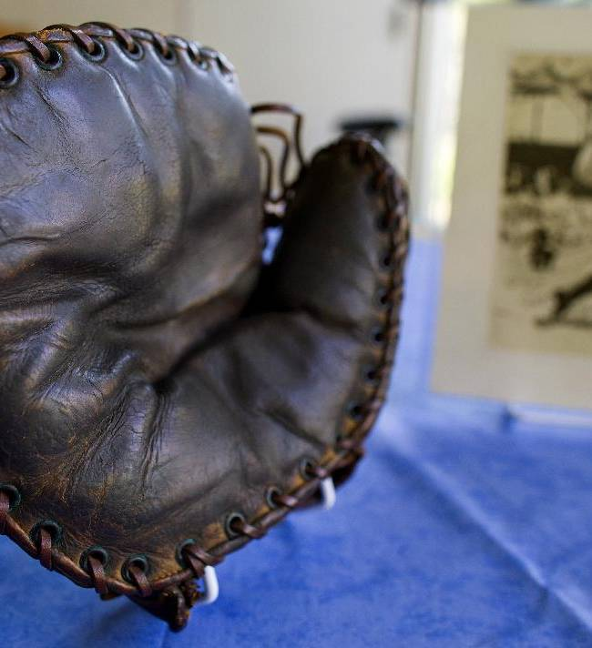 This photo taken on Monday, June 30, 2014, shows a Lou Gehrig signed baseball mitt and autographed picture given to Howard Henderson, who played catch with Gehrig as a boy, at Henderson's Greenwich, Conn., home Monday, June 30, 2104. Gehrig, a Yankee first baseman and a friend of Henderson's songwriter father, visited his home and Henderson visited him when he had ALS. The mitt that was autographed by Gehrig with a hot instrument, will be auctioned in July, expecting to fetch $200,000 to $300,000. (AP Photo/Craig Ruttle)