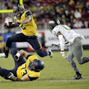 California running back Daniel Lasco, (2) leaps over teammate Jordan Rigsbee (73) as Oregon defensive back Troy Hill closes in during the second half of an NCAA college football game Friday, Oct. 24, 2014, in Santa Clara, Calif The Associated Press