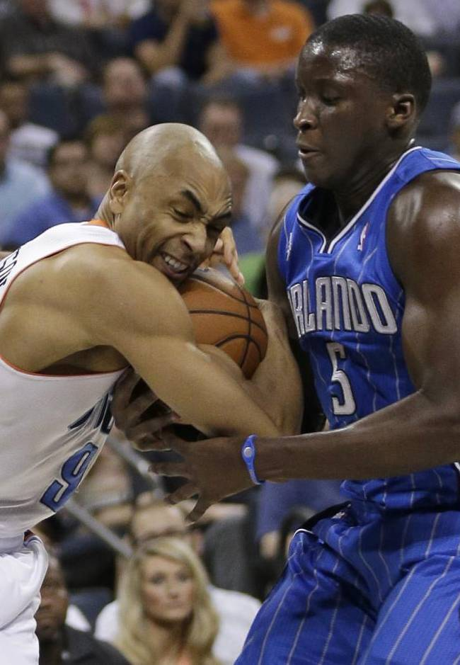 Charlotte Bobcats' Gerald Henderson, left, is fouled by Orlando Magic's Victor Oladipo, right, during the first half of an NBA basketball game in Charlotte, N.C., Friday, April 4, 2014