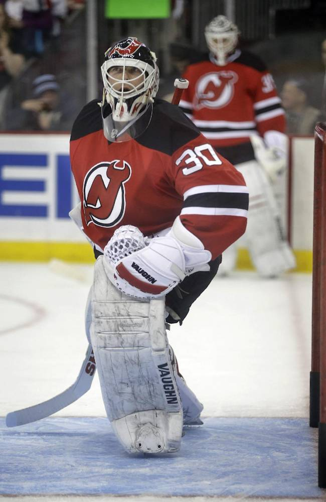 As fellow goalie Cory Schneider, background, looks on, New Jersey Devils goalie Martin Brodeur warms up in the goal before an NHL hockey game against the Boston Bruins in Newark, N.J., Sunday, April 13, 2014