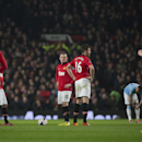 Manchester United's Wayne Rooney, center, and Michael Carrick, center right, wait with teammates for play to begin after a second goal by Manchester City's Edin Dzeko, out of frame, during their English Premier League soccer match at Old Trafford Stadium,