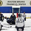 Boston Bruins defenseman Zdeno Chara (33) leans way back as he stretches at mid-ice with teammates during NHL hockey training camp in Wilmington, Mass., Friday, Sept. 19, 2014. (AP Photo/Elise Amendola)