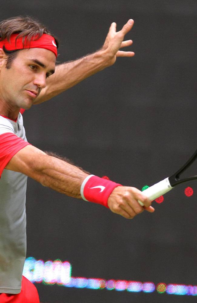 Swiss Roger Federer returns the ball to Portugal's Joao Sousa during the ATP tennis tournament in Halle, Germany, Thursday, June 12, 2014. Federer won the match with 6-7, 6-4 and 6-2