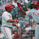 Philadelphia Phillies' Ben Revere, left, is congratulated by teammate Domonic Brown after Revere scored on a ground ball hit by Chase Utley Colorado Rockies in the eighth inning of the Phillies' 10-9 victory over the Colorado Rockies in a baseball game in