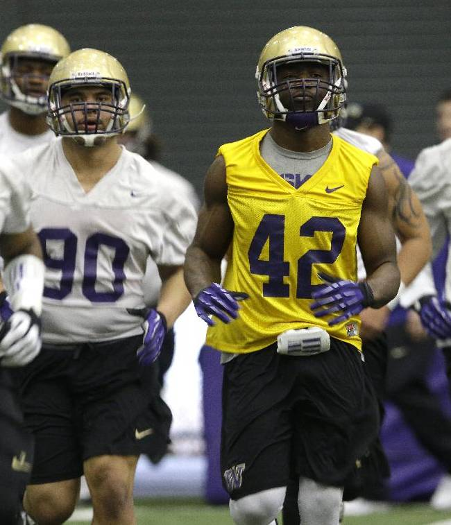 Washington NCAA college football players, including linebacker Cory Littleton (42) run during the first day of spring practice, Tuesday, March 4, 2014 in Seattle