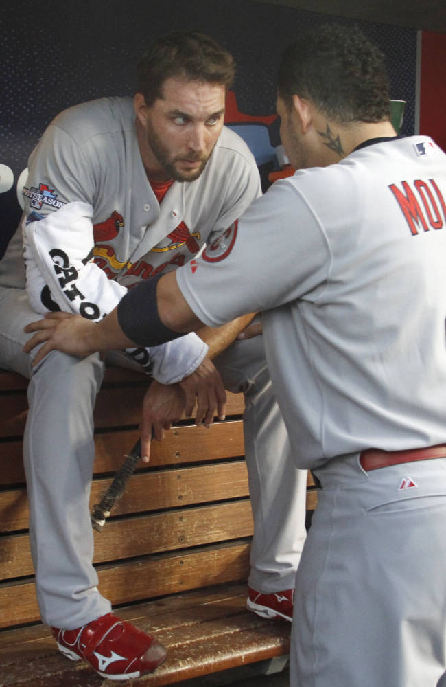 St. Louis Cardinals catcher Yadier Molina talks with starting pitcher Adam Wainwright in the dugout after Wainwright pitched the third inning during Game 3 of the National League Championship Series between the St. Louis Cardinals and the Los Angeles Dodgers on Monday, Oct. 14, 2013, at Dodger Stadium in Los Angeles