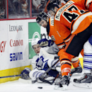 Toronto Maple Leafs' Peter Hollad, left, is pressed against the boards by Philadelphia Flyers' Carlo Colaiacovo, center, and Andew MacDonald, right, in the third period of an NHL hockey game, Saturday, Jan. 31, 2015, in Philadelphia. The Flyers won 1-0 Th
