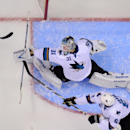 San Jose Sharks goalie Antti Niemi, top, of Finland, deflects a shot as defenseman Justin Braun reaches in during the first period in Game 3 of an NHL hockey first-round playoff series against the Los Angeles Kings, Tuesday, April 22, 2014, in Los Angele