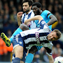 West Bromwich's Gareth McAuley tackled by Tottenham's Emmanuel Adebayor, behind, during the English Premier League soccer match between West Bromwich Albion and Tottenham Hotspur at The Hawthorns Stadium in West Bromwich, England, Saturday, April 12, 2014