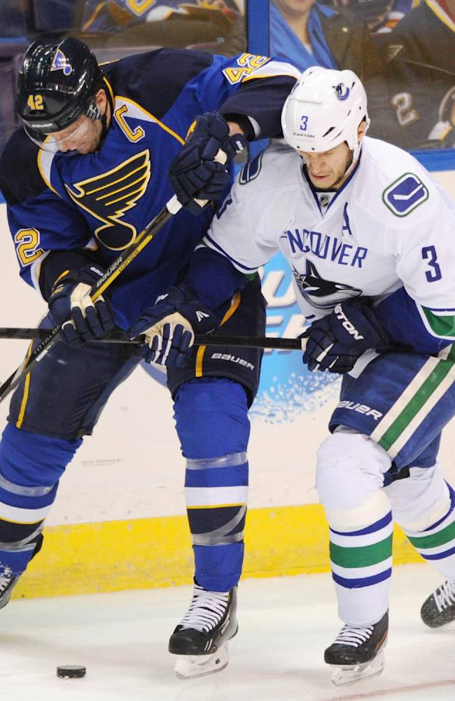 St. Louis Blues' David Backes (42) and Vancouver Canucks' Kevin Bieksa (3) battle for a loose puck during the second period of an NHL hockey game on Friday, Oct. 25, 2013, in St. Louis