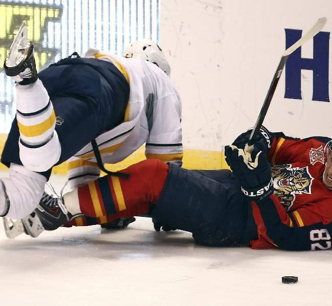 Buffalo Sabres' Nikita Zadorov, left, jumps over Florida Panthers' Tomas Kopecky as he tries to take control of the puck during the third period of an NHL hockey game in Sunrise, Fla., Friday, Oct. 25, 2013. The Sabres won 3-1