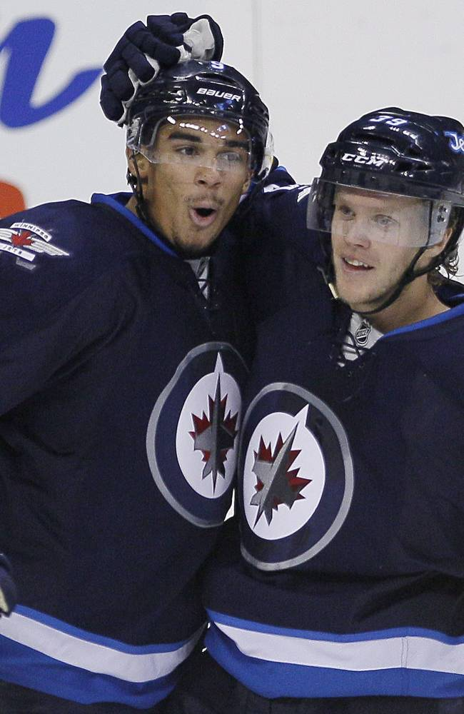 Winnipeg Jets' Evander Kane (9) and Toby Enstrom (39) celebrate Enstrom's game tying goal during the third period against the St. Louis Blues in an NHL hockey game Friday, Oct. 18, 2013 in Winnipeg, Manitoba