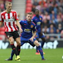 Sunderland's Seb Larsson, left, vies for the ball with Manchester United's Tom Cleverley, right, during their English Premier League soccer match at the Stadium of Light, Sunderland, England, Sunday, Aug. 24, 2014