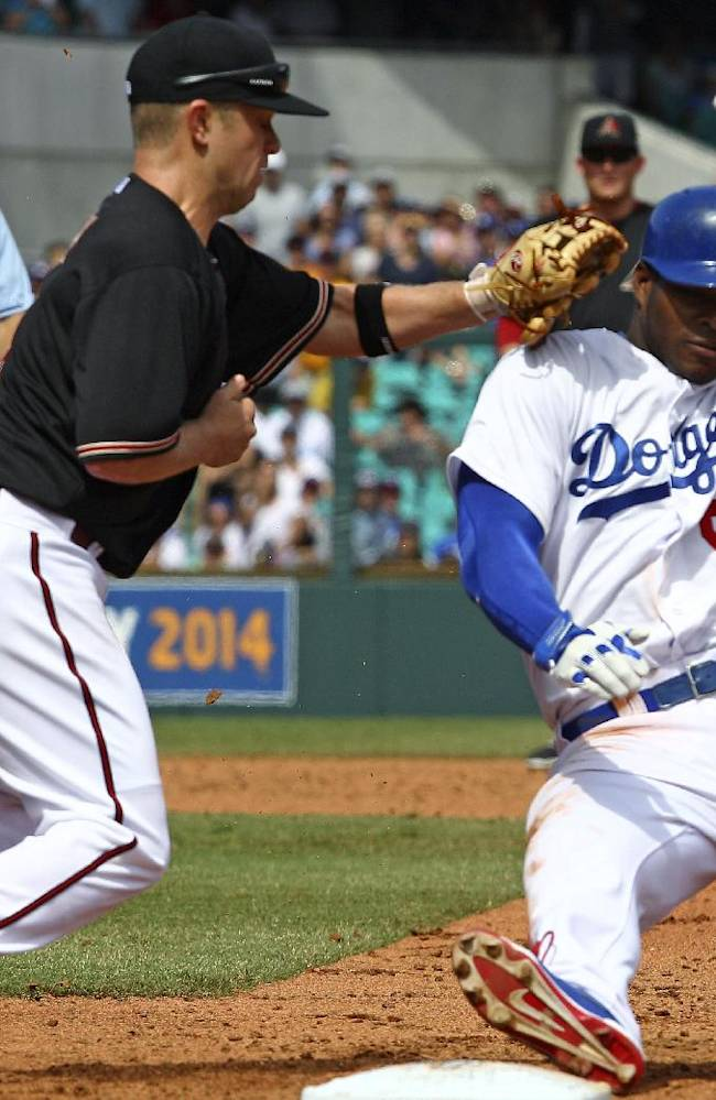 Los Angeles Dodgers' Yasiel Puig, right, is tagged out by the Arizona Diamondbacks' Aaron Hill during a run down in the second game of the two-game Major League Baseball opening series between the Los Angeles Dodgers and Arizona Diamondbacks at the Sydney Cricket ground in Sydney, Sunday, March 23, 2014. The Dodgers won the game 7-5 and the series 2-0