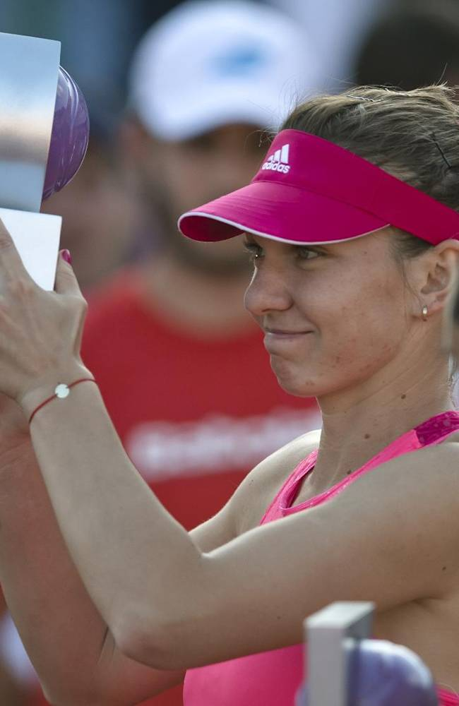 Romania' Simona Halep, left, lifts the trophy after defeating Italy's Roberta Vinci, right, in the singles final match of a WTA Bucharest Open women's tennis tournament in Bucharest, Romania, Sunday, July 13, 2014