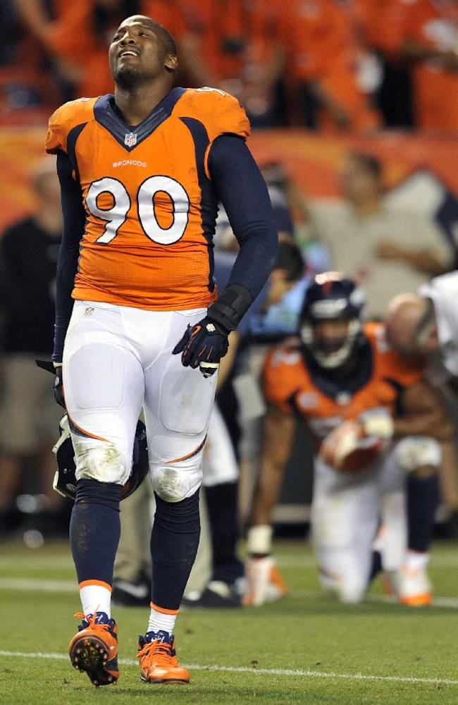 Denver Broncos outside linebacker Shaun Phillips (90) walks off the field after teammate Danny Trevathan, rear, fumbled at the goal line during the second half of an NFL football game against the Baltimore Ravens, Thursday, Sept. 5, 2013, in Denver