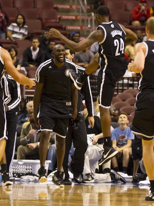 Brooklyn Nets' Chris Johnson celebrates with teammates as time is called during the fourth quarter of a preseason NBA basketball game against the Philadelphia 76ers, Monday, Oct. 14, 2013, in Philadelphia.  The Nets won 127-97