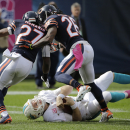 Chicago Bears cornerbacks Sherrick McManis (27) and Tim Jennings (26) knock down Miami Dolphins quarterback Ryan Tannehill during the second half of an NFL football game Sunday, Oct. 19, 2014 in Chicago The Associated Press