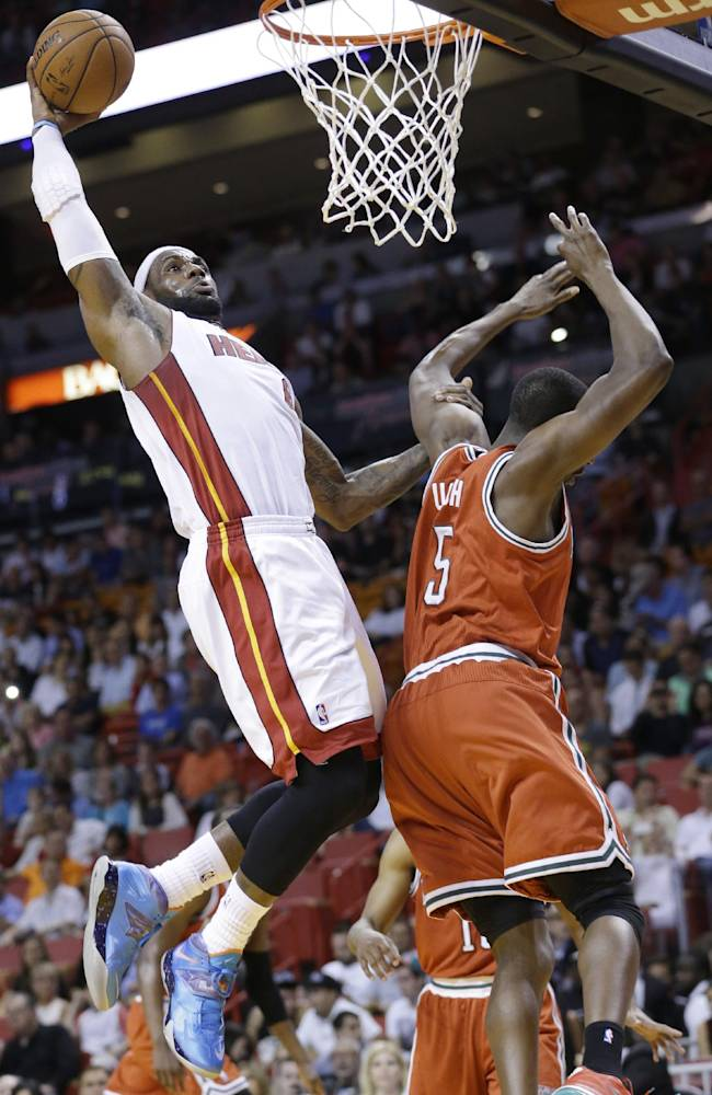 Miami Heat forward LeBron James, left, dunks against Milwaukee Bucks forward Ekpe Udoh (5) during the first half of an NBA basketball game on Wednesday, April 2, 2014, in Miami