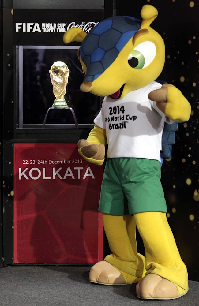 An Indian man dressed as Fuleco, mascot for the 2014 World Cup soccer tournament, stands near the trophy after unveiling it for public display in Kolkata, India, Monday, Dec. 23, 2013. The 18 carat gold trophy weighing 6.175kg (14lb) has been brought to the country as part of the global FIFA World Cup Trophy Tour