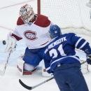 Montreal Canadiens goaltender Carey Price, left, makes a save on a shot by Toronto Maple Leafs' James van Riemsdyk during second-period NHL hockey game action in Toronto, Wednesday, Oct. 8, 2014 The Associated Press