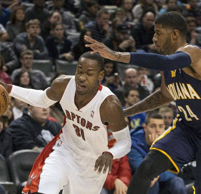 Toronto Raptors' Terrance Ross, left, drives at Indiana Pacers' Paul George during the first half of an NBA basketball game in Toronto on Wednesday, Jan. 1 , 2014