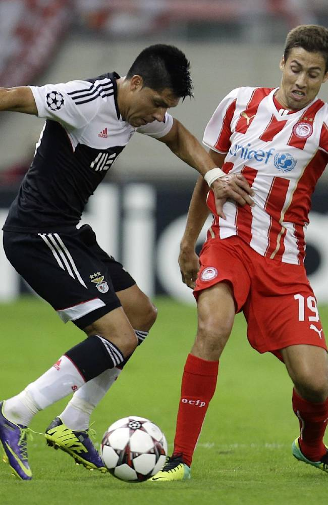 Olympiakos' David Fuster, right, and Benfica's Enzo Perez fight for the ball during their Champions League group C soccer match at the Karaiskaki stadium, in the port of Piraeus, near Athens, Tuesday, Nov. 5, 2013