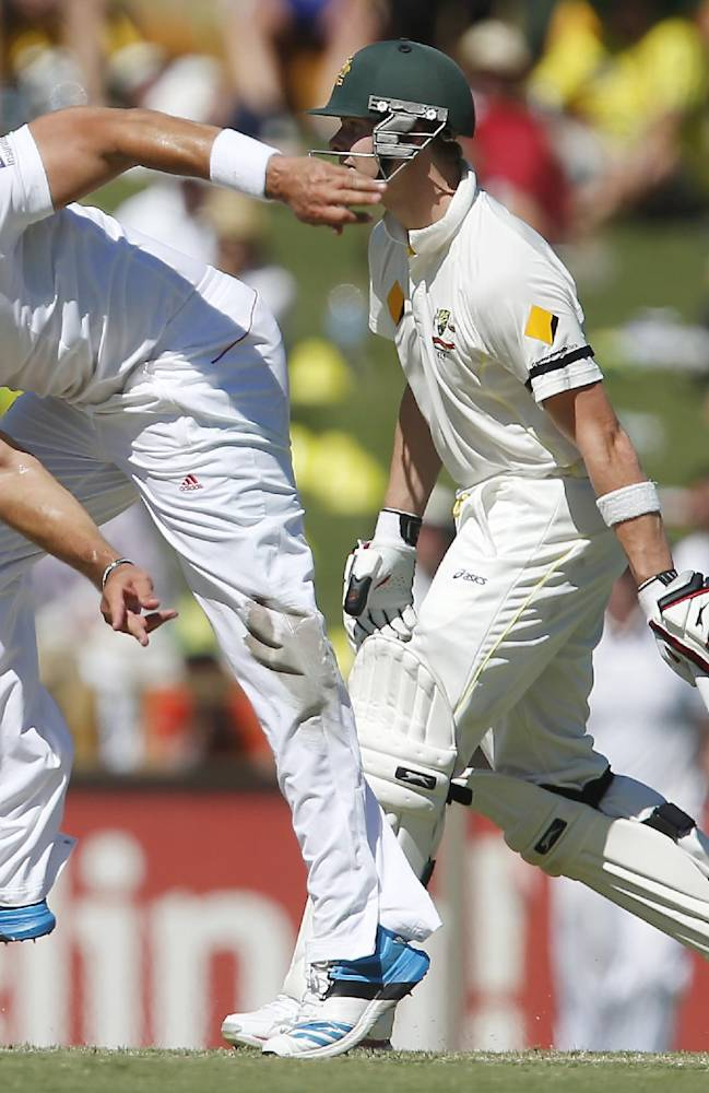 England's Tim Bresnan, left, bowls a delivery as Australia's Steve Smith, right, watches on during the first day of play during the Ashes test match in Perth, Australia, Friday, Dec. 13, 2013