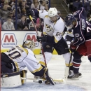 Nashville Predators' Chris Mason, left, makes a save as teammate Victor Bartley, center, and Columbus Blue Jackets' Vinny Pro