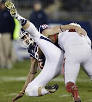 Connecticut punter Cole Wagner, right, is hit by Louisville's Brandon Radcliff, right, on a blocked punt during the first half of an NCAA college football game, in East Hartford, Conn., Friday, Nov. 8, 2013. (AP Photo/Charles Krupa)