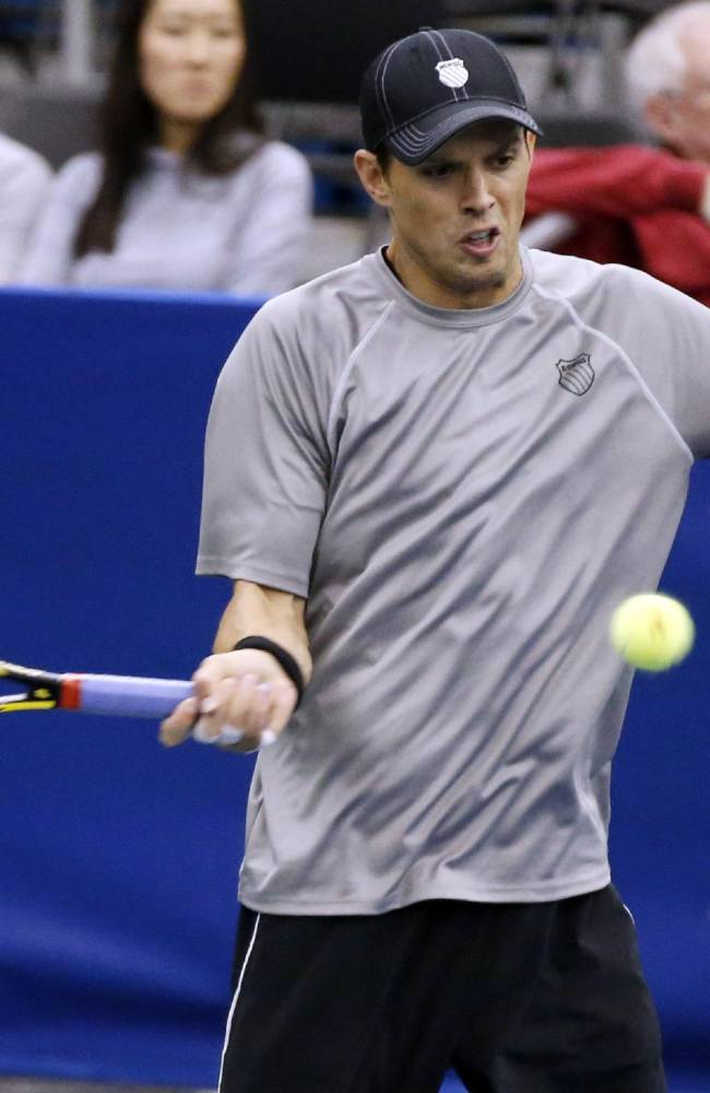 Mike Bryan hits a return to the doubles team of Raven Klaasen, of South Africa, and Eric Butorac in the finals at the U.S. National Indoor Tennis Championships, Sunday, Feb. 16, 2014, in Memphis, Tenn. Klaasen and Butorac won 6-4, 6-4