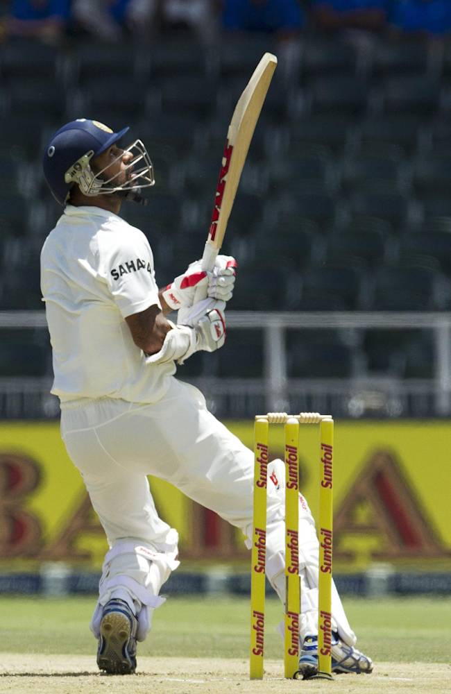 India's batsman Shikhar Dhawan, watches his shot during the first day of their cricket test match against South Africa at Wanderers stadium in Johannesburg, South Africa, Wednesday, Dec. 18, 2013
