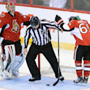 A linesman fishes the puck from the net as Ottawa Senators' Craig Anderson, left, and Erik Karlsson stands during the third period of an NHL hockey game in Ottawa, Ontario, Sunday, Nov. 17, 2013 The Associated Press
