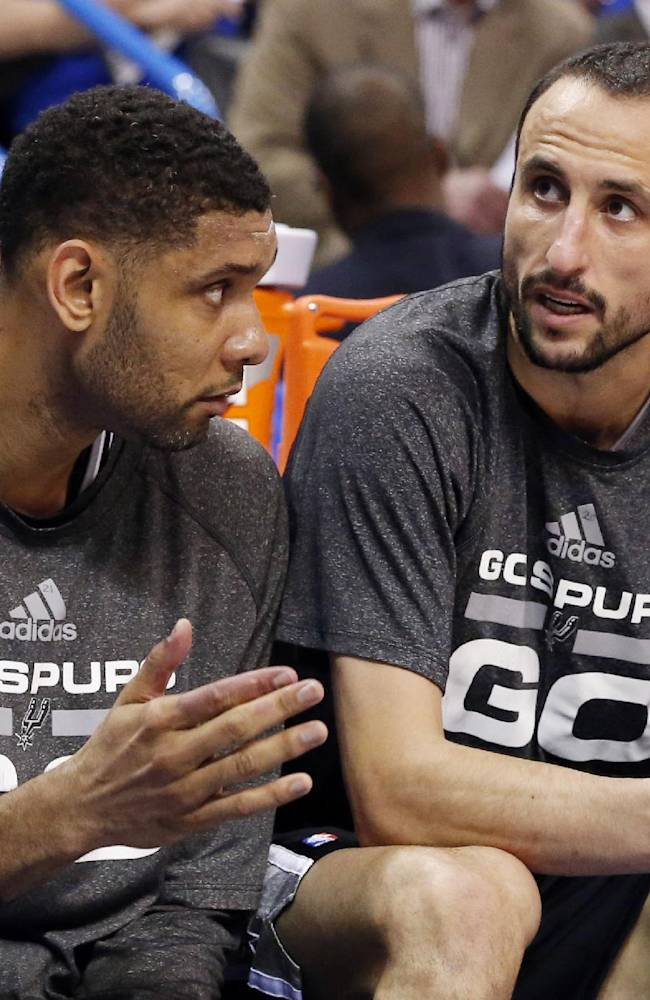San Antonio Spurs forward Tim Duncan, left, talks with teammate Manu Ginobili in the fourth quarter of Game 3 of an NBA basketball playoff series against the Oklahoma City Thunder in the Western Conference finals, Sunday, May 25, 2014, in Oklahoma City. Oklahoma City won 106-97